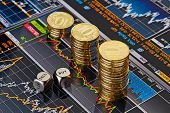 stock photo of coin bank  - Dices cubes with the words SELL BUY downtrend stacks of golden coins - JPG
