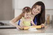 foto of babysitter  - Cute baby girl and her mother having fun in the kitchen - JPG