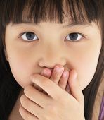 stock photo of shy girl  - Scared little girl covering mouth with hand - JPG