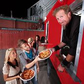 stock photo of food truck  - Food truck owner serving pizza to happy couple - JPG