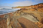 stock photo of hollow point  - Pebble Beach and tafoni formations in Pigeon Point formation sandstone at Bean Hollow State Beach in San Mateo County California against a blue sky and white clouds - JPG