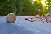 stock photo of restriction  - This national forest road is blocked by a land slide of rock and debris to where it is a hazard for drivers in cars - JPG