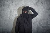 stock photo of scumbag  - Confused burglar concept thief with balaclava caught and arrested in front of the grunge concrete wall - JPG