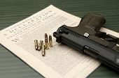 stock photo of ammo  - A close up of a hand gun with bullets resting on the Declaration of Independence - JPG