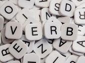 stock photo of verbs  - Verb letters spelled on white letter tiles - JPG