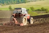 Photo Of Red Tractor Working The Ground