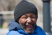 stock photo of bums  - Happy and smiling homeless african american man outdoors during the day - JPG