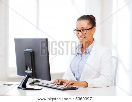 business and internet concept - smiling african businesswoman with computer in office