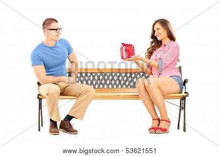 Young female giving a gift box to her boyfriend, seated on a bench, isolated on white background