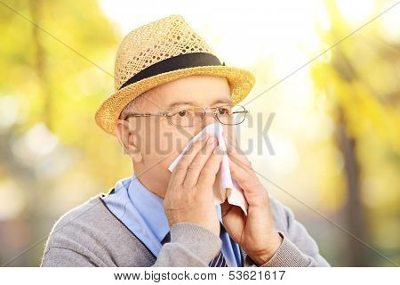 Mature man blowing his nose in tissue paper because of being ill or allergy outside