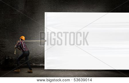 Image of woman engineer pulling blank white banner