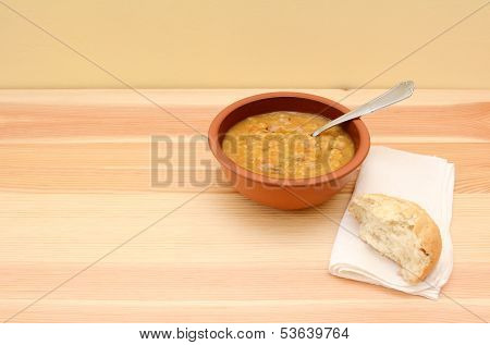 Serving Of Chunky Vegetable Soup And Half A Bread Roll