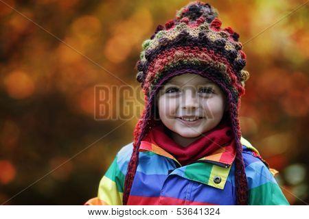 Little boy in Autumn park wearing a warm beanie hat