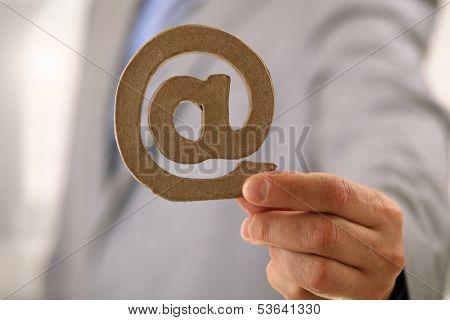 Businessman holding an e-mail address at symbol
