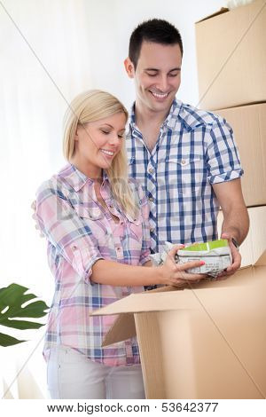 Young couple unpacking dishes in new home