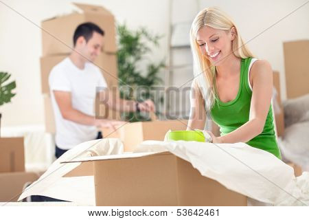young couple unpacking moving boxes in a living room