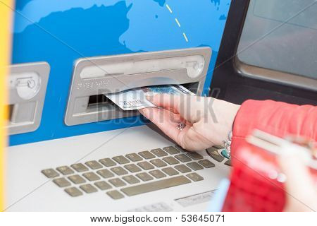 Woman taking banknotes from a bank ATM or automatic teller machine removing the bills from the slot as the machine dispenses them