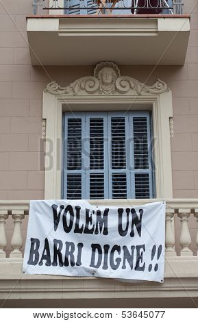 Protest banner hanging off the balustrade on a building facade saying Volem Un Barri Digne, or We Want A Decent Neighbourhood as residents demonstrate regarding their lifestyle and living conditions