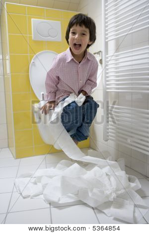 Little Boy Is Making Fun With Toiletpaper In The Bathroom