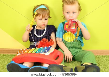 Little boy and girl sitting at the bright green wall and playing on a toy trumpet and metallophone