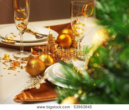 Photo of luxury Christmastime table setting, holiday dinner in restaurant, festive white dinnerware decorated with pretty golden balls and ribbons, warm candle light, green Christmas tree in room