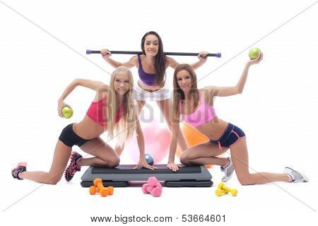 Cheerful sportswomen with gymnastic equipment