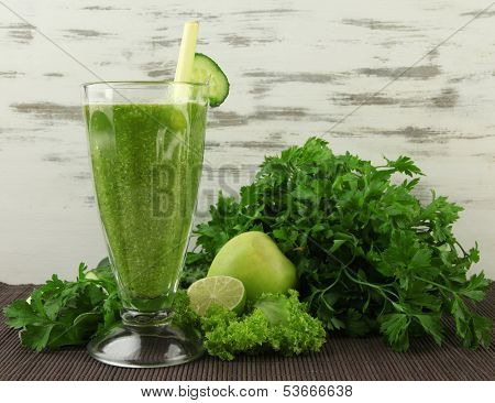 Glasses of green vegetable juice on bamboo mat on wooden background