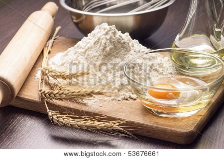 Baking Ingredients With Wheat Ears On Wood Board