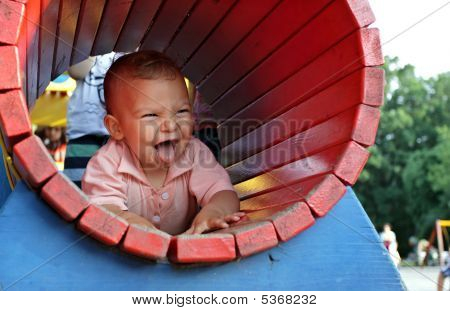 Happy Kid In A Playground Tunnel