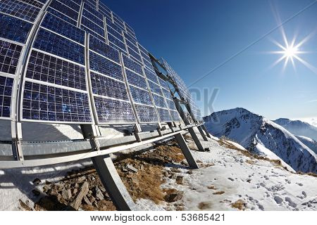 Big cluster of solar panels on a mountain peak