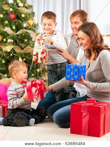 Christmas Big Family with Children near the Christmas Tree at home. Happy Children Opening Gift.