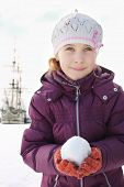 picture of snowball-fight  - The girl in a cap and gloves holding snowball next to a sailboat - JPG