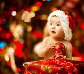 stock photo of ball cap  - Christmas baby in Santa hat holding red ball near present gift box - JPG