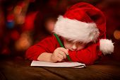 stock photo of miracle  - Christmas child writing letter in red Santa hat - JPG