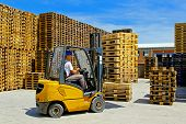 stock photo of wooden pallet  - Forklift operator handling wooden pallets in warehouse - JPG