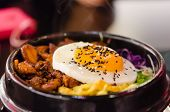 stock photo of kimchi  - closeup bibimbap with fried egg in a heated stone bowl korean style food - JPG
