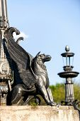 pic of metal sculpture  - sculpture of griffin on stone pedestal in autumn sunny day - JPG