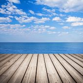 stock photo of dock a lake  - Empty wooden pier with sea and cloudy sky on background - JPG