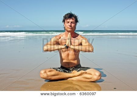 Young handsome man meditating on the beach sitting in lotus position