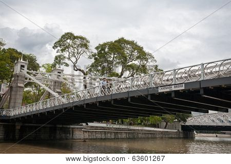 SINGAPORE - NOVEMBER 05, 2012: Pedestrian Cavenagh Bridge is the only suspension bridge,it is the oldest bridge in Singapore,in lower reaches of the Singapore River in the Downtown. Opened in 1869.