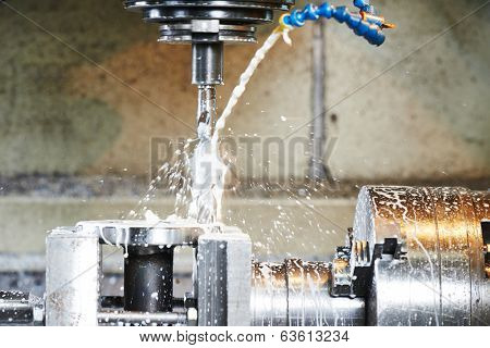 drilling hole or boring detail with lubricant liquid coolant on metal cutting machine tool at factory