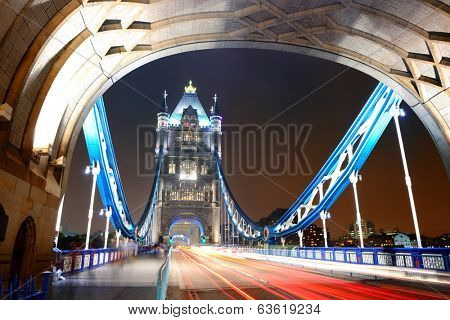 Tower Bridge in London with busy traffic at night.