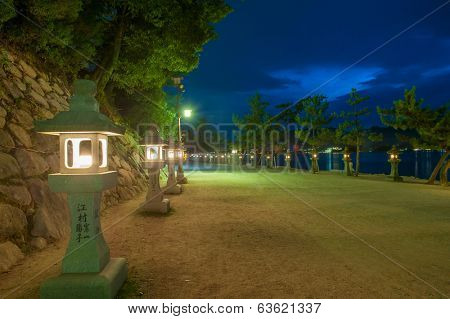 Path on Miyajima island near Itsukushima shinto shrine, Japan shortly after the sunset with a row of lit lanterns on the shore