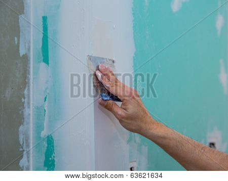 drywall hydrophobic plasterboard in green plastering seam with trowel