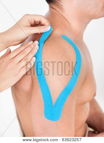 Person Applying Physio Tape To Man
