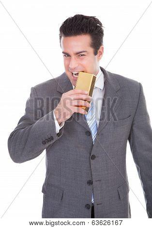 Businessman Biting Gold Bar