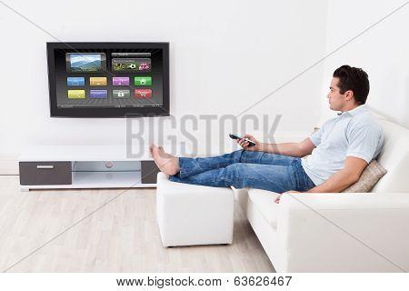 Man Applying Settings On Television