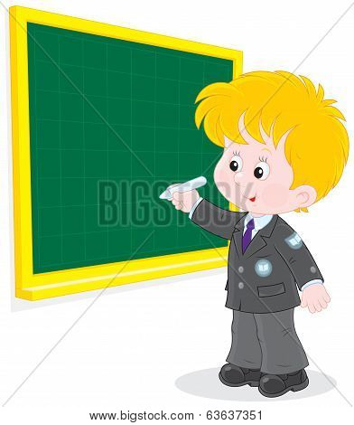 Schoolboy writes on the blackboard