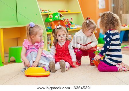Little girls playing with toys in  playroom