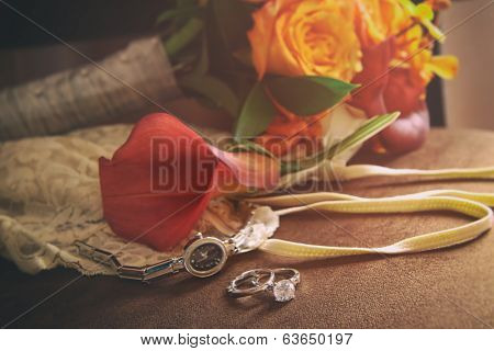 Wedding rings and accessories on velvet chair